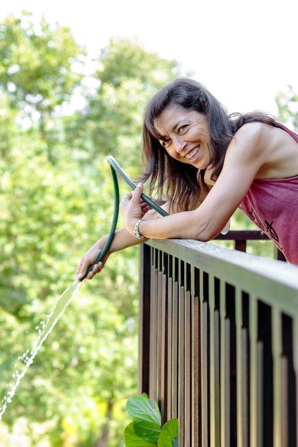 Stående av den lyckliga mogna kvinnan som bevattnar växterna arkivbild