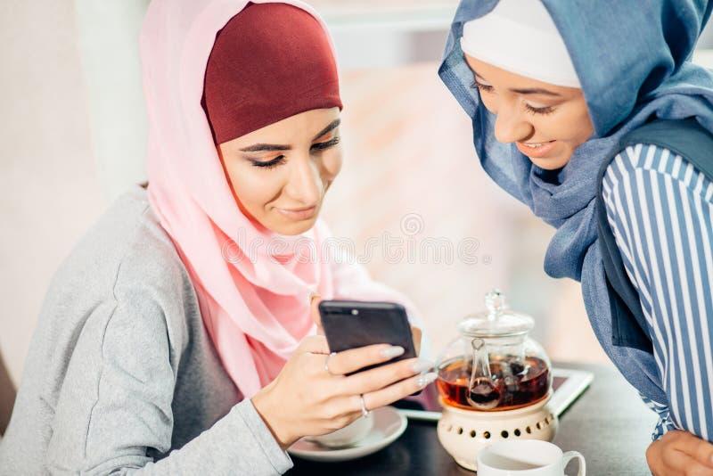 Stående av den lyckliga muslimkvinnan som använder mobiltelefonen, medan sitta på en soffa royaltyfri fotografi