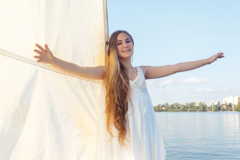 Stående av den lyckliga nätta flickan med den vita klänningen och lång lockig bl arkivbilder