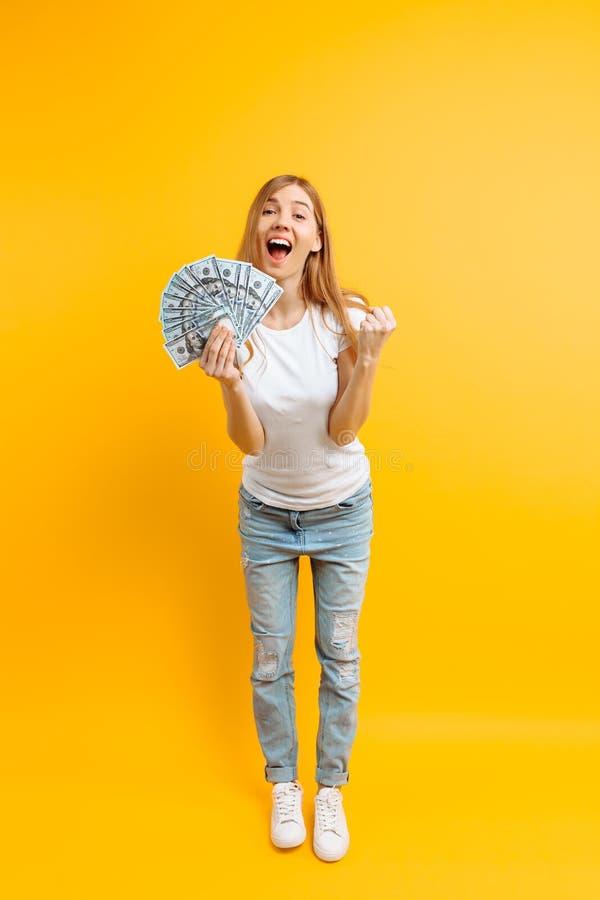 Stående av den lyckliga nöjda flickan med en grupp av sedlar och firasegern och framgång över gul bakgrund arkivfoton