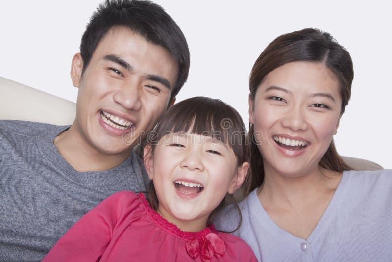 Stående av den lyckliga och le familjen i tillfälliga kläder, studioskott, lutande fotografering för bildbyråer