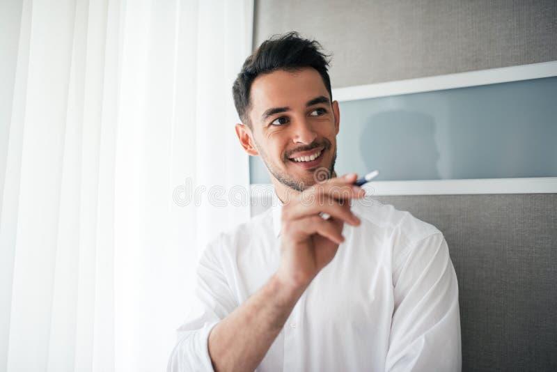 Stående av den lyckliga och le stiliga affärsmanvisningen eller poiting något med en penna och att se en sida i kontoret arkivfoton