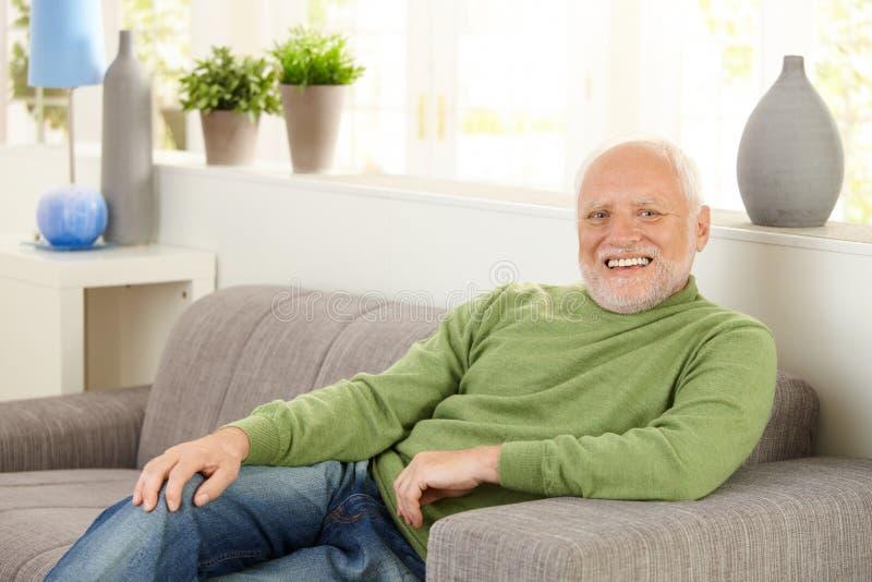 Stående av den lyckliga pensionären på sofaen arkivbild