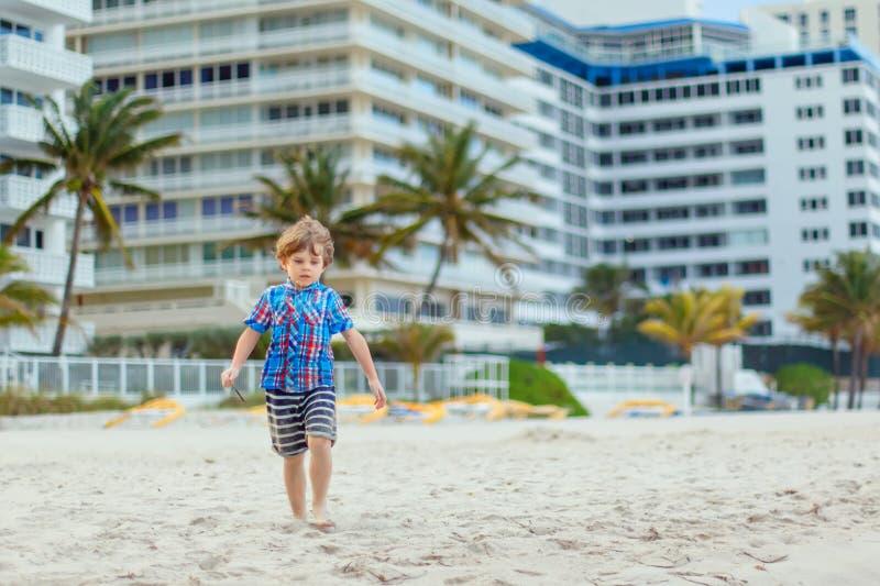Stående av den lyckliga pojken för liten unge på stranden av havet Rolig gullig barndanande semestrar och tycka om sommar Sunt arkivbild