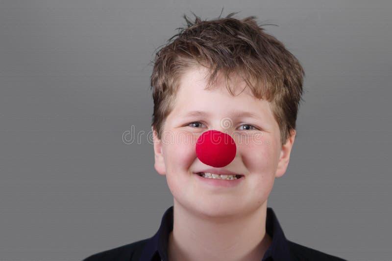 Stående av den lyckliga pojken med den röda näsan royaltyfri foto