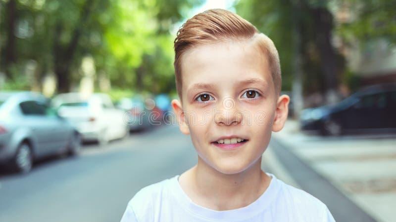 Stående av den lyckliga pojken med kall hipsterfrisyr - charma den unga tillfälliga le ungen med den moderiktiga frisyren royaltyfri bild