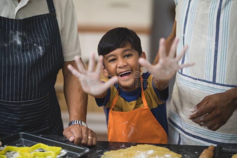 Stående av den lyckliga pojken som visar smutsiga händer, medan förbereda mat med fadern och farfadern arkivfoton