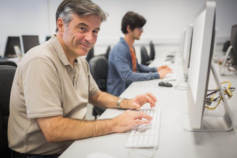 Stående av den lyckliga professorn som arbetar på datoren arkivbild