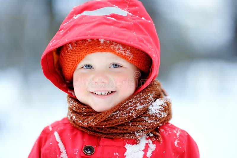 Stående av den lyckliga pysen i röd vinterkläder som har gyckel under snöfall royaltyfri fotografi