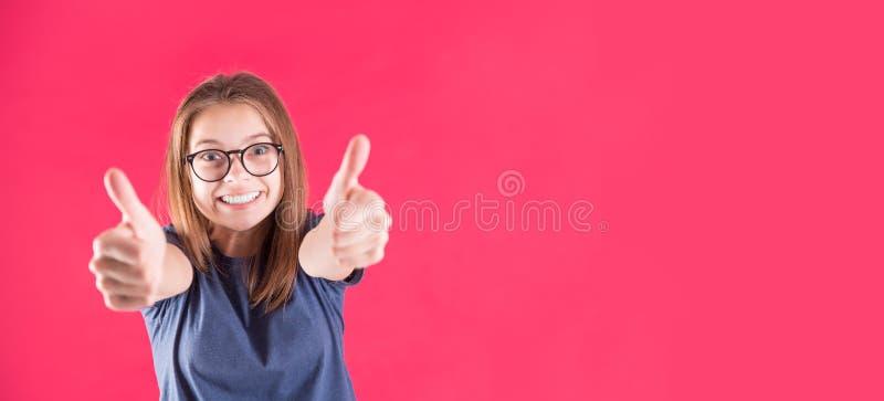 Stående av den lyckliga roliga tonåriga flickan över röd bakgrund arkivbild