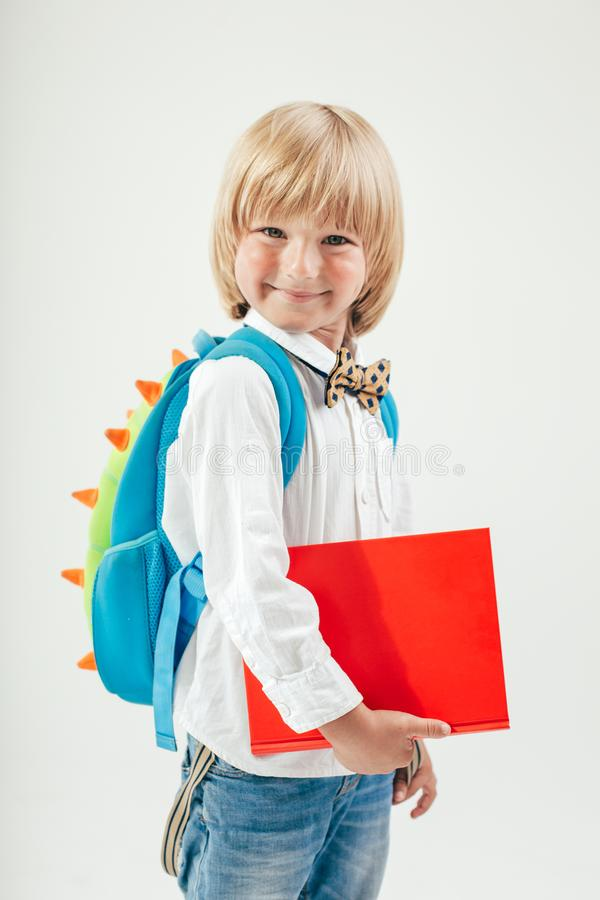 Stående av den lyckliga skolpojken med böcker och äpplet som isoleras på vit bakgrund Utbildning som isoleras royaltyfri bild