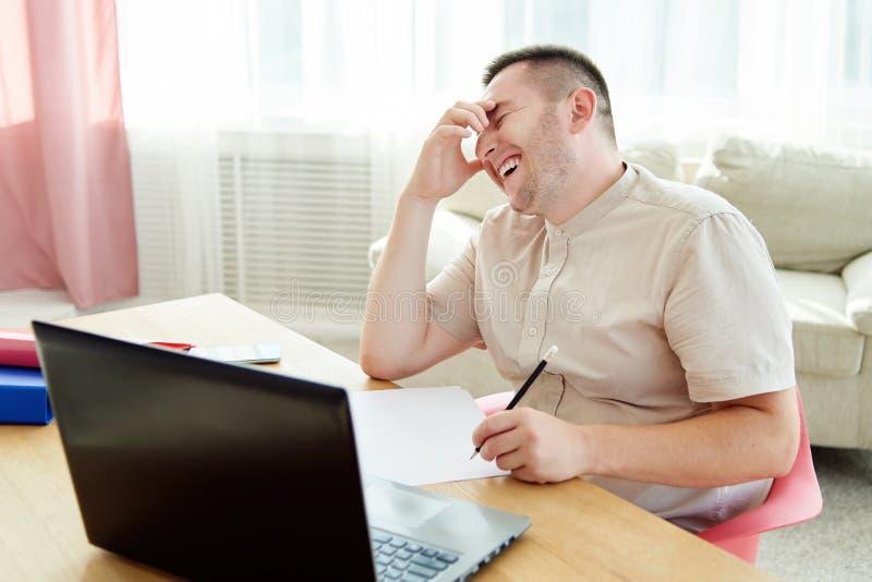 Stående av den lyckliga skratta affärsmannen som sitter på träskrivbordet och att arbeta med dokument och bärbara datorn i modern royaltyfri foto