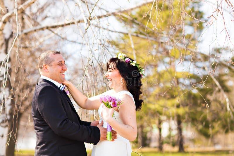 Stående av den lyckliga skratta bruden och brudgummen på gatan på den soliga dagen arkivfoto