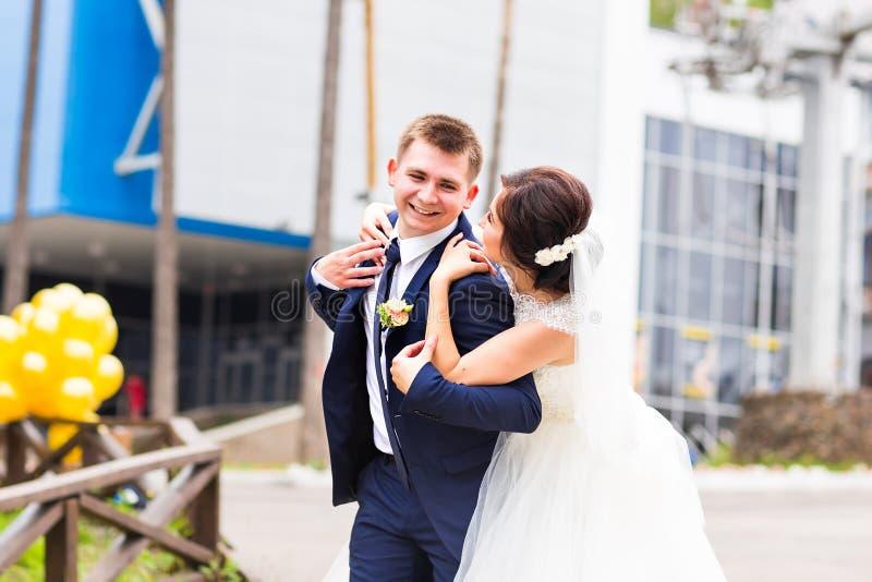 Stående av den lyckliga skratta bruden och brudgummen på gatan på den soliga dagen fotografering för bildbyråer
