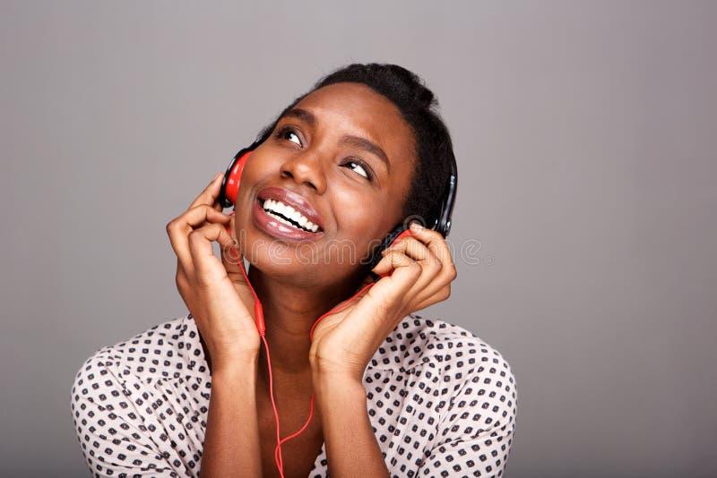 Stående av den lyckliga svarta kvinnan som lyssnar till musik på hörlurar arkivbilder