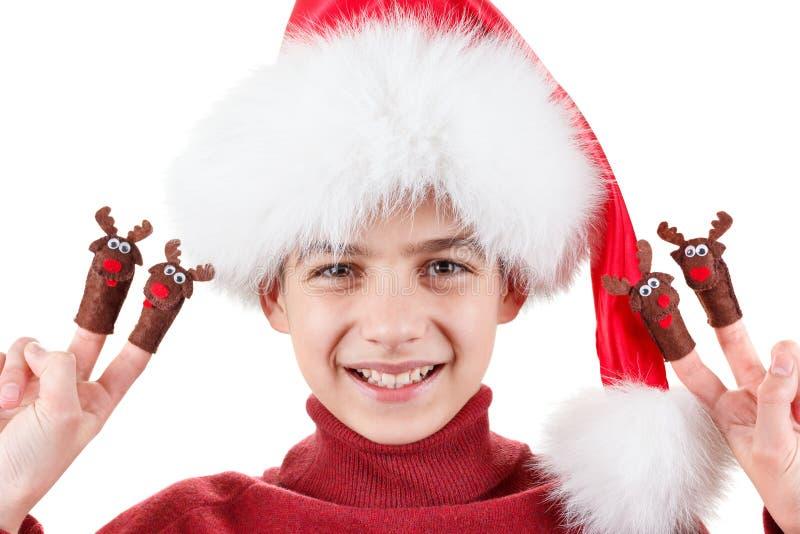 Stående av den lyckliga tonåriga pojken i jultomtenhatt med hjortleksaken som isoleras upp på vit royaltyfria bilder
