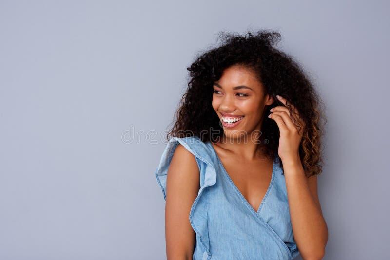 Stående av den lyckliga unga afrikansk amerikankvinnan som ler mot grå bakgrund arkivfoton