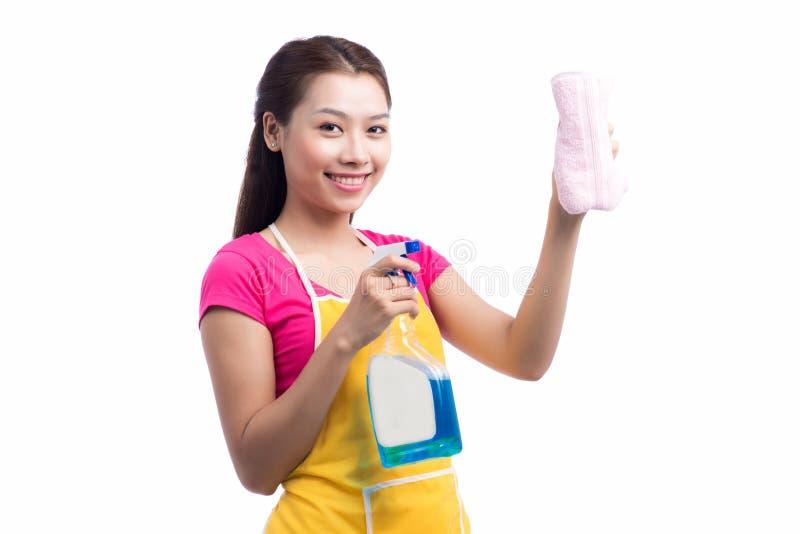 Stående av den lyckliga unga asiatiska hembiträdeCleaning Glass With svampen royaltyfri foto