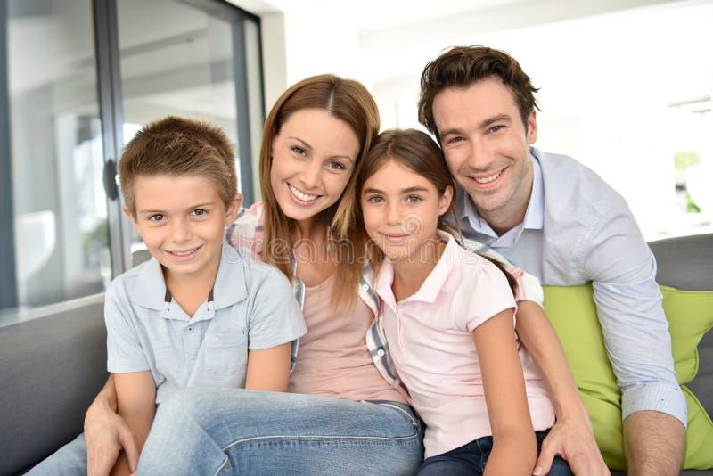 Stående av den lyckliga unga familjen med hemmastadda barn arkivfoton