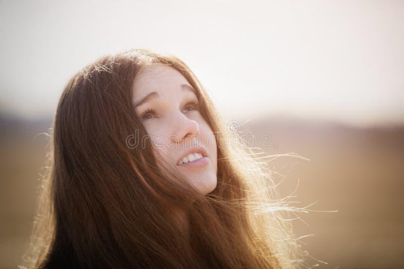 Stående av den lyckliga unga flickan som ser till himlen på vårfält fotografering för bildbyråer