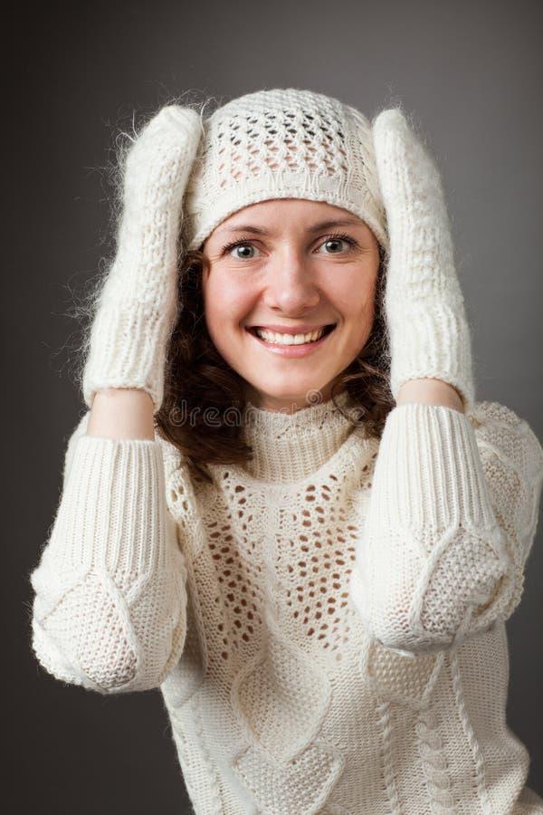 Stående av den lyckliga unga kvinnan i den vita hatten och tumvanten royaltyfria bilder