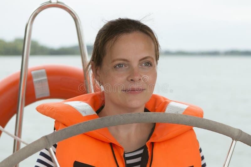 Stående av den lyckliga unga kvinnan i flytväst med styrninghjulet på yachten royaltyfria foton