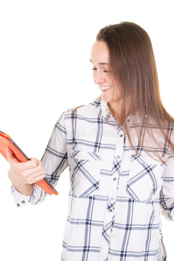 Stående av den lyckliga unga kvinnan i tillfällig kläder genom att använda minnestavlan som isoleras mot vit bakgrund som ler den arkivfoto
