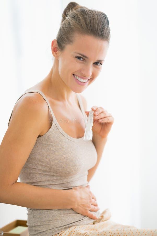 Stående av den lyckliga unga kvinnan med graviditetstestet arkivfoto