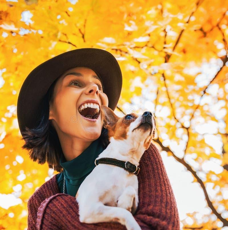 Stående av den lyckliga unga kvinnan med hunden utomhus i höstlookin arkivfoto