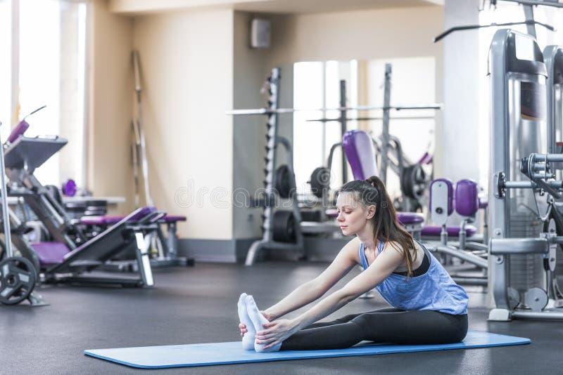 Stående av den lyckliga unga kvinnan som gör sträcka övning i idrottshall royaltyfria bilder
