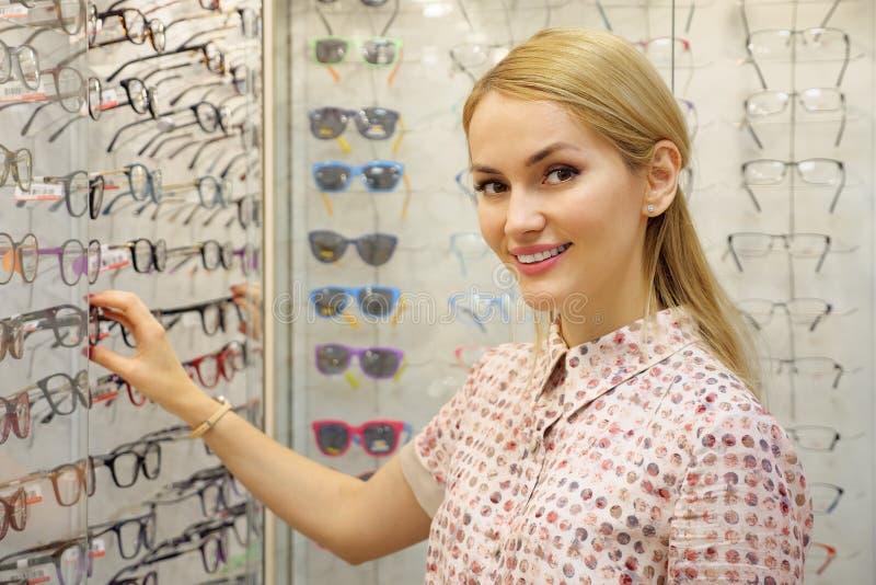 Stående av den lyckliga unga kvinnan som köper nya exponeringsglas på optikerlagret arkivfoton