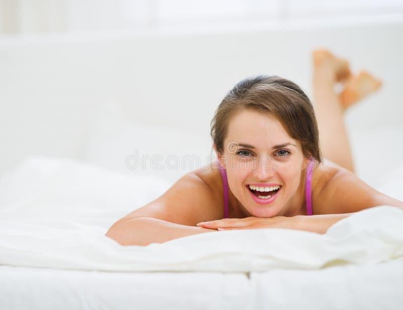 Stående av den lyckliga unga kvinnan som lägger på underlag royaltyfri foto