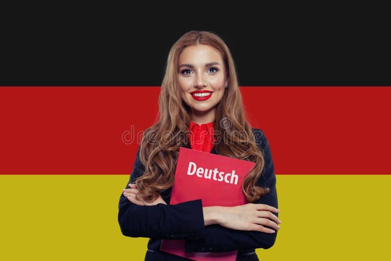 Stående av den lyckliga unga kvinnan som ler mot Tysklandflaggan arkivbild