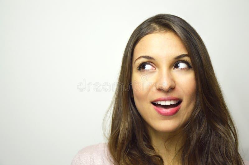 Stående av den lyckliga unga kvinnan som ser till sidan med kuriositet på vit bakgrund kopiera avstånd fotografering för bildbyråer