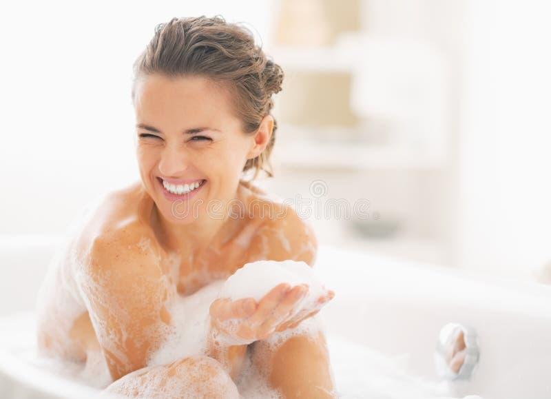Stående av den lyckliga unga kvinnan som spelar med skum i badkar royaltyfri bild