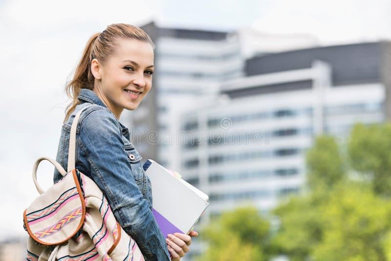 Stående av den lyckliga unga kvinnliga studenten på högskolauniversitetsområdet arkivfoto