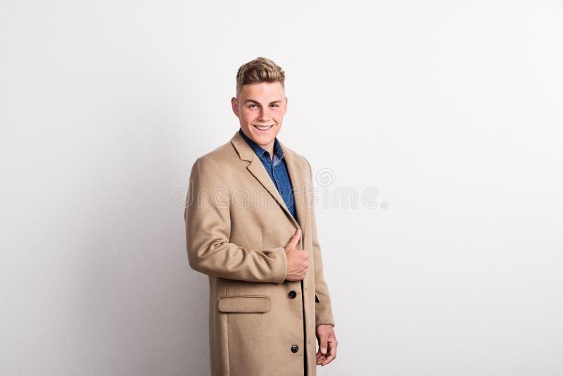 Stående av den lyckliga unga mannen i en studio, bärande brunt lag kopiera avstånd royaltyfria bilder