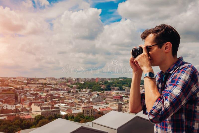 Stående av den lyckliga unga mannen, turist med kameran som tar bilder av den gamla staden Lviv från synvinkel royaltyfria foton