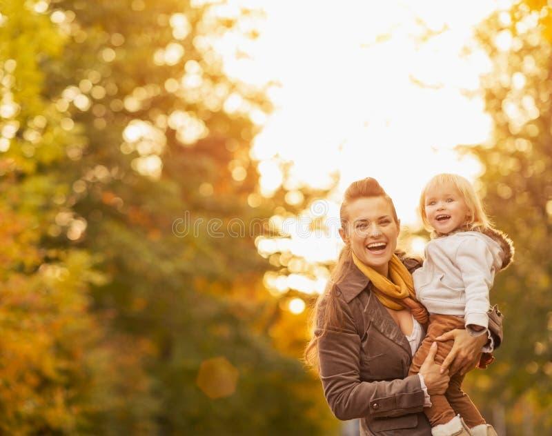 Stående av den lyckliga unga modern och behandla som ett barn utomhus royaltyfria foton