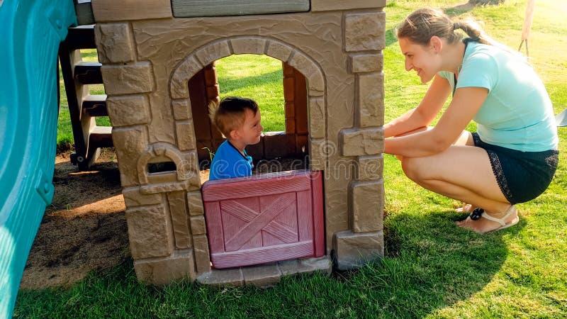 Stående av den lyckliga unga modern som ser hennes skratta litet barnpojke som spelar i leksakhus på lekplatsen fotografering för bildbyråer