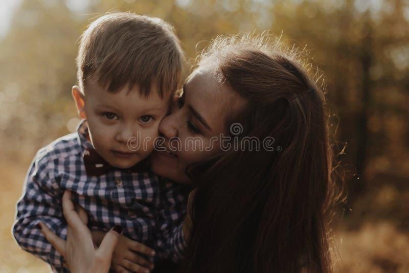 Stående av den lyckliga unga pojken för handsom med hans mamma Mamman kysser hans händer Sonen ser kameran och le arkivfoto