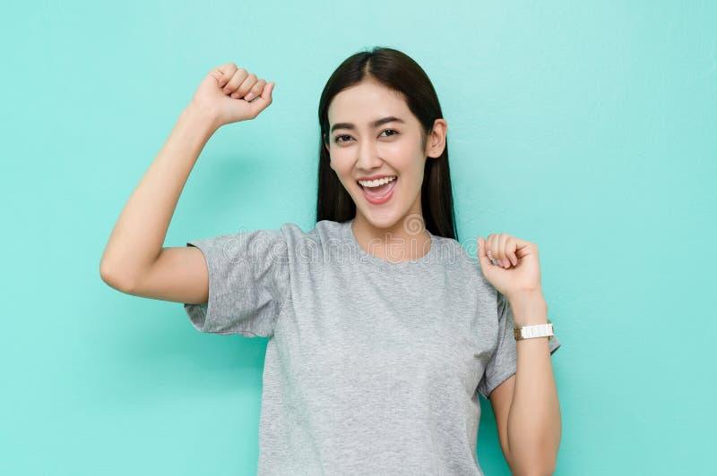 Stående av den lyckliga upphetsade asiatiska kvinnan i grå t-skjorta som skriker och triumferar med lyftta händer på grön pastell royaltyfri foto