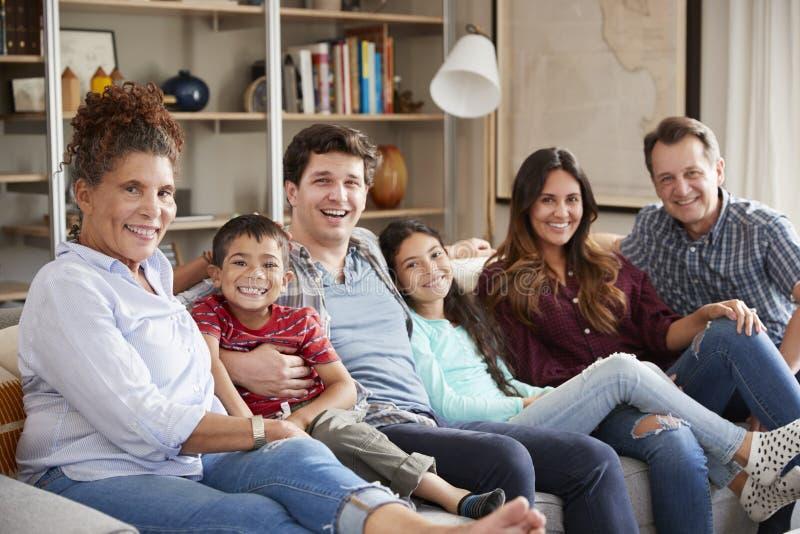 Stående av den mång- utvecklingsfamiljen som kopplar av på Sofa At Home Together royaltyfri foto