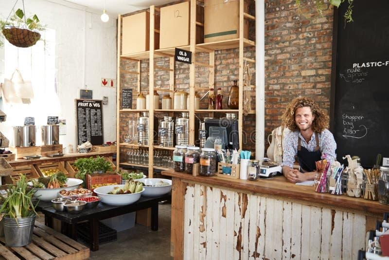 Stående av den manliga ägaren av den hållbara plast- fria livsmedelsbutiken bak försäljningsskrivbordet arkivfoto