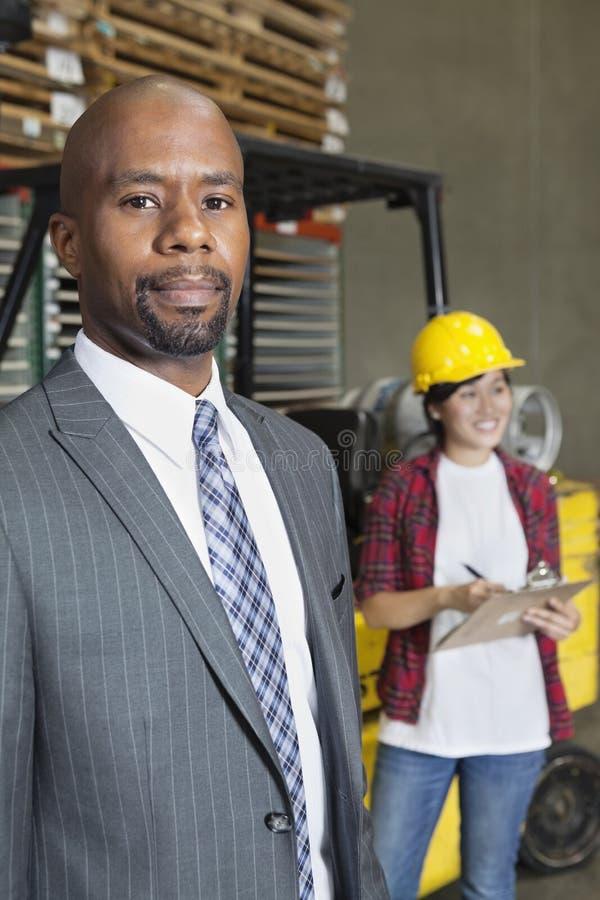 Stående av den manliga affärsmannen för säker afrikansk amerikan med anseende för kvinnlig arbetare i bakgrund royaltyfri fotografi