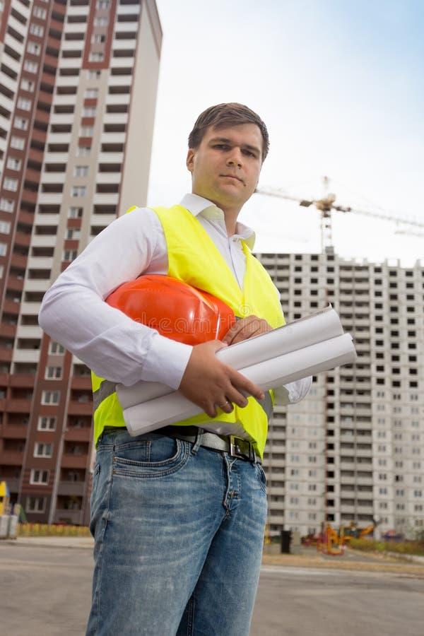 Stående av den manliga arkitekten som poserar med ritningar mot byggnader under construciton arkivfoto