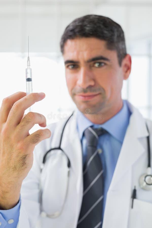 Stående av den manliga doktorn som rymmer en injektion arkivfoton