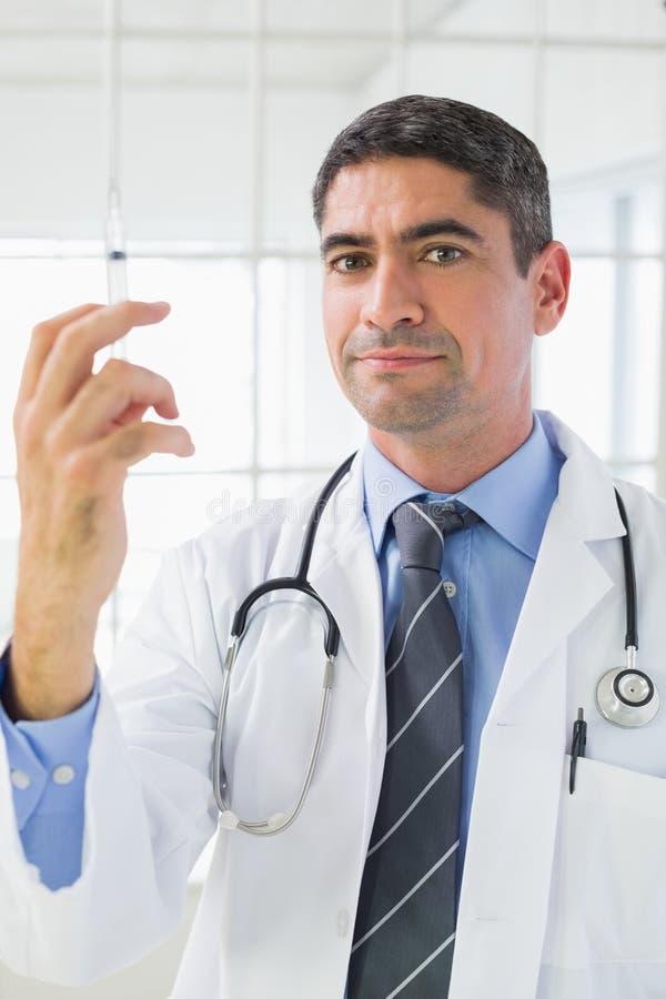 Stående av den manliga doktorn som rymmer en injektion royaltyfria foton