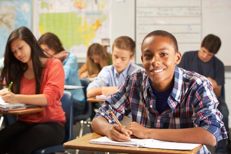 Stående av den manliga eleven som studerar på skrivbordet i klassrum royaltyfri bild