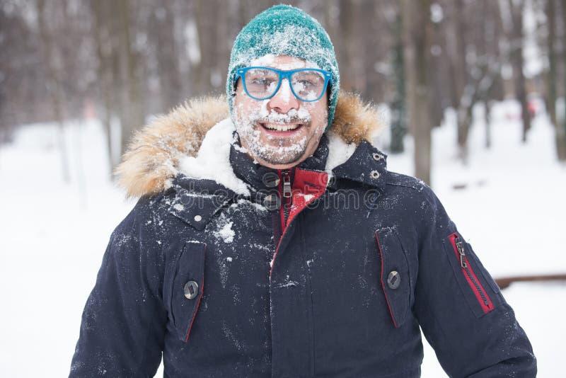 Stående av den manliga framsidan som täckas med snö Galet gladlynt, roligt, royaltyfri fotografi